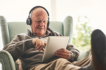 Elderly man with headphone reading a tablet in a comfy chair